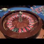Roulette Wheel Spinning in Las Vegas Casino the Dealer Croupier Rims the ball and Marks Winning Spot